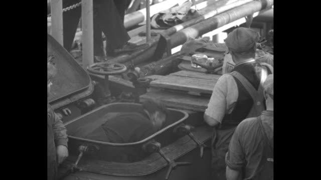 vídeos y material grabado en eventos de stock de ms raritan sun tanker at dock / closer shot of raritan sun stern / man standing in hold pulling out sacks of liquor and tossing them onto pallet /... - estribo de coche