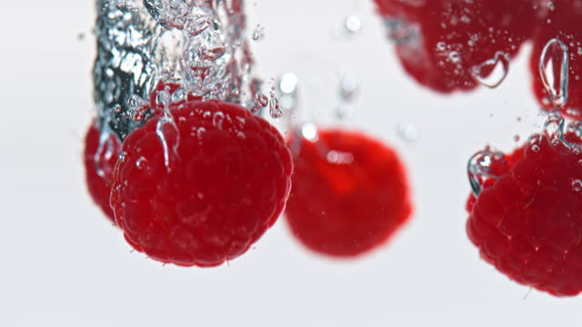 slo mo ld raspberries falling into water - raspberry stock videos & royalty-free footage