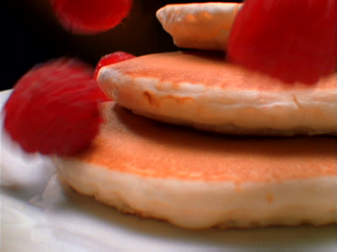 raspberries falling onto pancakes - パンケーキ点の映像素材/bロール
