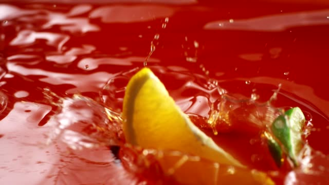 raspberry, orange and lime pieces falling into juice. splash crown - raspberry stock videos and b-roll footage