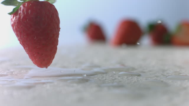 Raspberry rolls through mist on wet surface