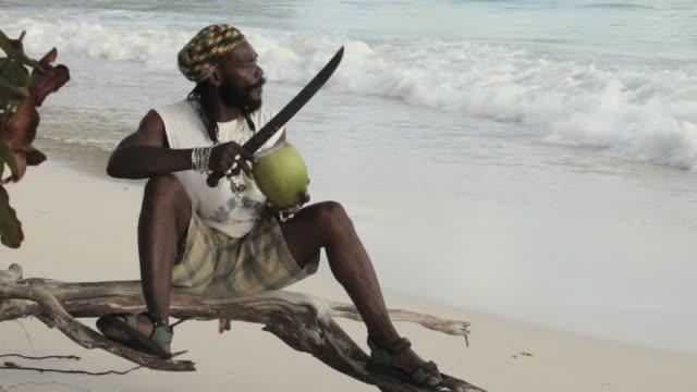 WS Rasta man on beach cutting and drinking coconut / Oistins, Christ Church, Barbados
