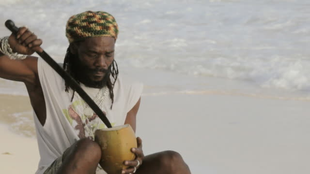 ms rasta man on beach cutting and drinking coconut / oistins, christ church, barbados - rastafarian stock videos & royalty-free footage