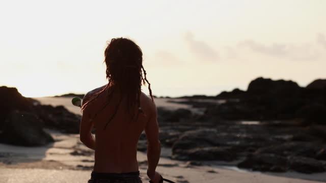vídeos de stock, filmes e b-roll de ms rasta man spinnin poi balls on beach and walking towards / montezuma, punteranes, costa rica - kelly mason videos