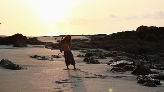 vídeos de stock, filmes e b-roll de ms rasta man spinning poi balls behind his back on beach with sunrise / montezuma, punteranes, costa rica - kelly mason videos