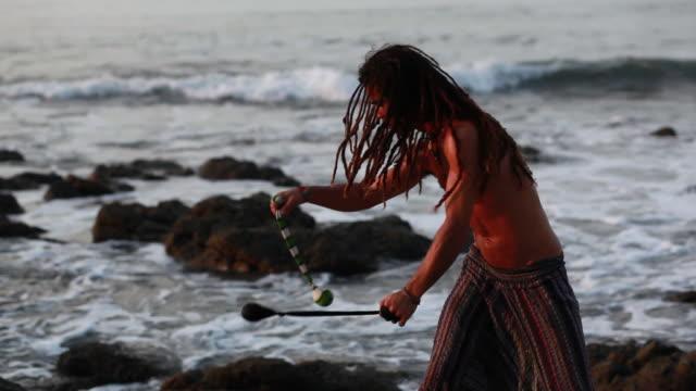 ms ts rasta man spinninig poi balls with ocean / montezuma, punteranes, costa rica - kelly mason videos stock-videos und b-roll-filmmaterial