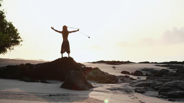 vídeos de stock, filmes e b-roll de ms rasta man wearing glasses standing on rock spinning poi balls with sunrise / montezuma, punteranes, costa rica - kelly mason videos
