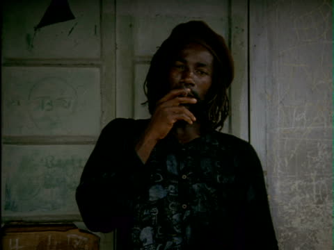 rastafarian men wearing dreadlocks in backyard smoking marijuana from pipe and large joints. men smoking marijuana on january 01, 1992 in jamaica - dreadlocks stock videos & royalty-free footage