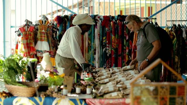 vídeos de stock e filmes b-roll de a rastafarian sells medicinal herbs and moringa at a local market in martinique - feirante