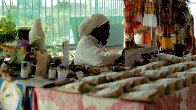 a rastafarian sells medicinal herbs and moringa at a local market in martinique - rastafarian stock videos & royalty-free footage