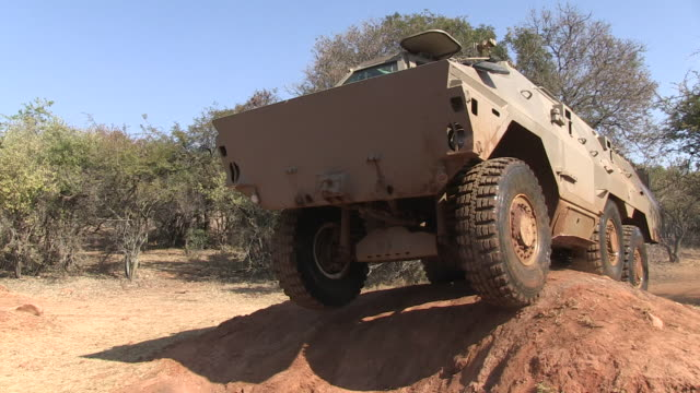 ratel military vehicle drives through muddy water. - durevolezza video stock e b–roll