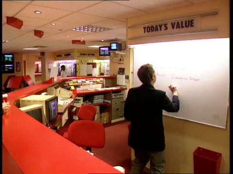 vídeos de stock e filmes b-roll de ratings war between 'eastenders' and 'coronation street' england ms man writing on white board cms street 1/6 as hand writes up bookie's odds - eastenders