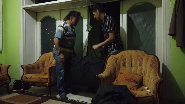 vidéos et rushes de rauf and son shakib of afghanistan weigh their luggage in a doorway in preparation for their flight to the united states after the families asylum... - non us film location
