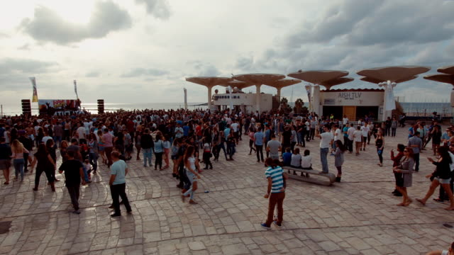 ew/s rave party on a public square in tel aviv at the sea site. - イスラエル点の映像素材/bロール