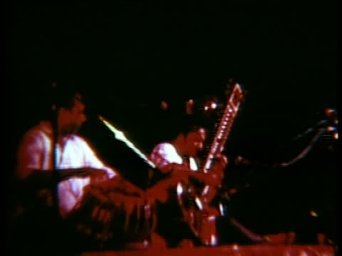 Ravi Shankar playing sitar beside man with drums onstage at Woodstock music festival/ Bethel New York USA