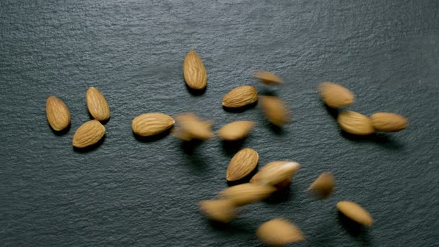 Raw Almonds on Slate in Slow Motion
