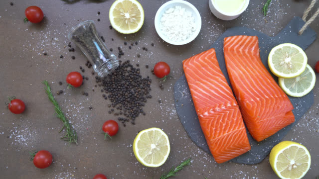 Raw and fresh salmon meat fillet on black stone slate