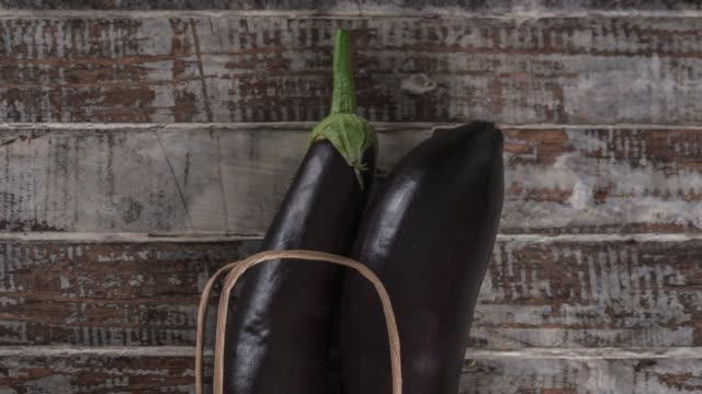 raw aubergine on the wood background - aubergine stock videos & royalty-free footage