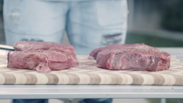 生の牛肉ステーキは、味付けされている炭グリルから煙を通して撮影され、夏の夕方に裏庭で夕食のためにバーベキューで調理する準備ができています - 低炭水化物ダイエット点の映像素材/bロール