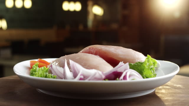 Raw chicken breast on plate with lettuce, onion and tomato