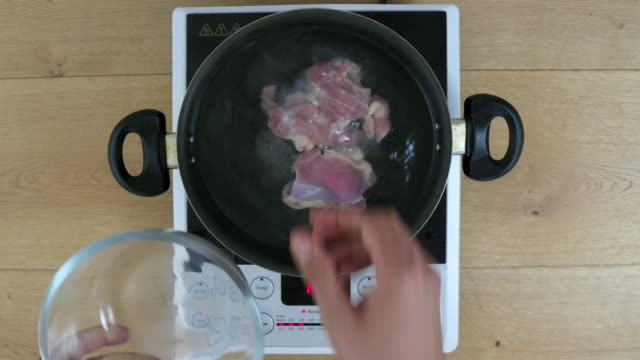 Raw chicken breasts being put inside a cooking pan with boiling water