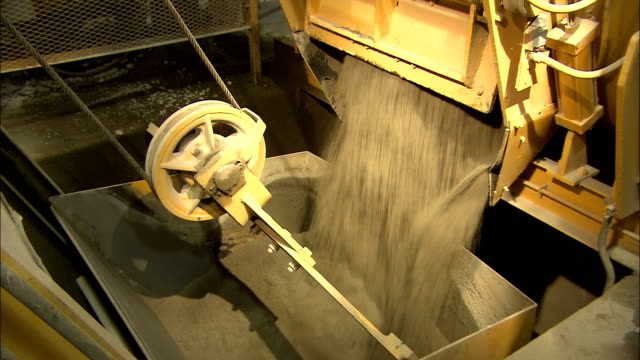 raw materials for cement fall down a chute into a bin. - cement stock videos & royalty-free footage