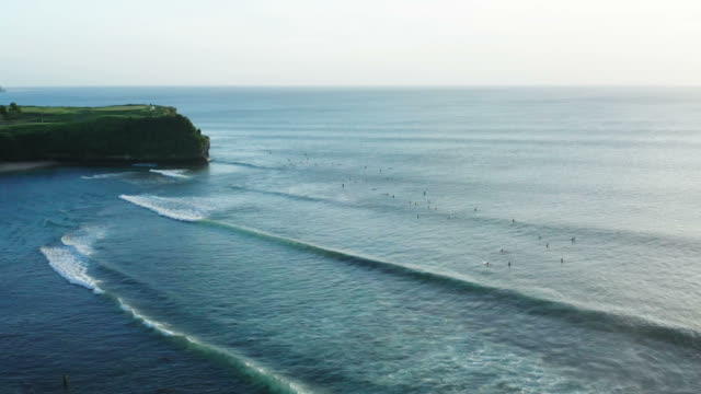 raw of tidal waves with group of surfers in bali - tide stock videos & royalty-free footage