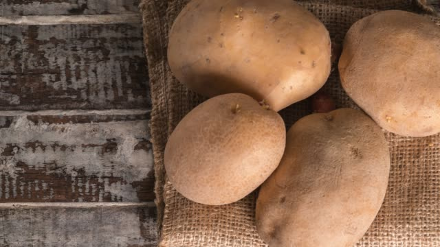 raw potatoes on an old wood table - raw food stock videos & royalty-free footage