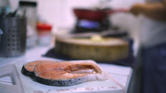 vídeos de stock e filmes b-roll de raw salmon in kitchen - filete de salmão