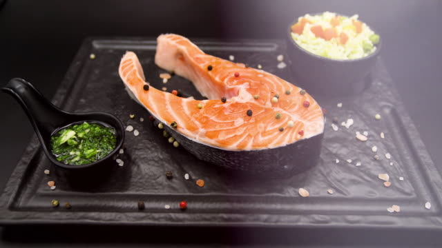 raw salmon steak isolated on black background - salmon salad stock videos & royalty-free footage