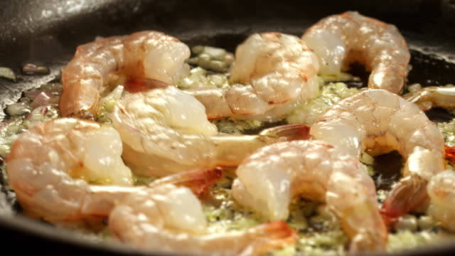 vídeos de stock, filmes e b-roll de ms raw shrimp in frying pan being sauteed with olive oil and herbs while skillet is shaken  - skillet cooking pan