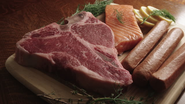 raw t-bone beef steak, hot dogs, and salmon gourmet food on a cutting board - steak stock videos & royalty-free footage