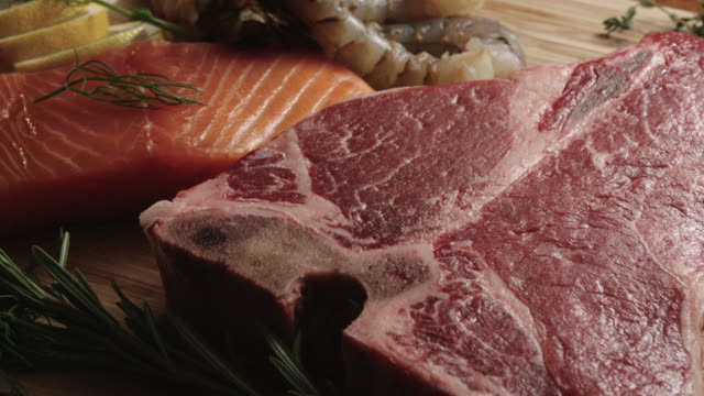 raw t-bone beef steak, shrimp, and salmon gourmet food - cutting board stock videos and b-roll footage