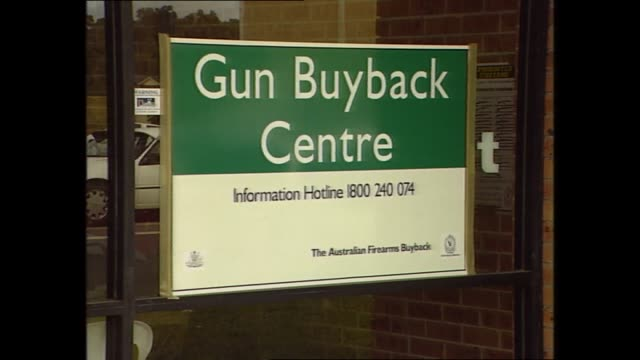 raw vision of guns buy back centre: various signs advertising the gun buy back centre alternating with various shots of exterior of centre - gun stock videos & royalty-free footage