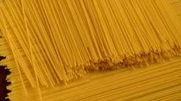 Raw yellow long spaghetti.Thin pasta arranged in rows.