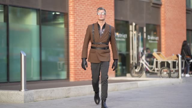 rayer van ristell wears sunglasses a brown blazer jacket black leather belts a vuitton belt black leather gloves striped pants black leather shoes... - striped stock videos & royalty-free footage