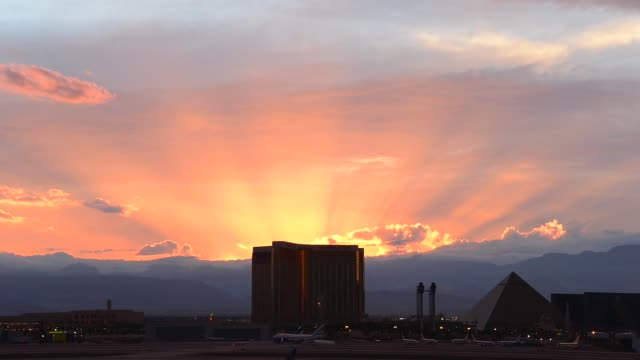 Rays from the setting sun break through storm clouds west of the Mandalay Bay Resort and Casino and the Luxor Hotel and Casino on August 25 2013 in...