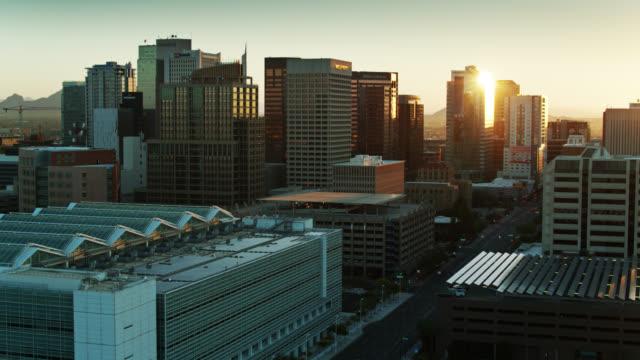 rays of rising sun shining between skyscrapers in phoenix - aerial view - phoenix arizona stock videos & royalty-free footage