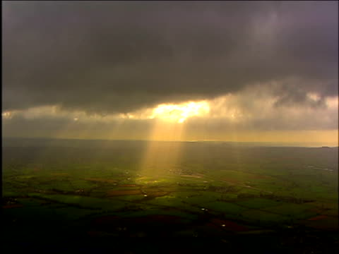rays of sun break through thick cloud over countryside england - sunbeam stock videos & royalty-free footage