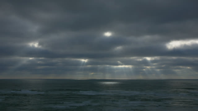 time lapse wide shot rays of sunlight shine through heavy cloud cover over ocean - oregon coast stock videos & royalty-free footage