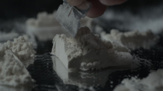 Razor blade cutting pile of cocaine