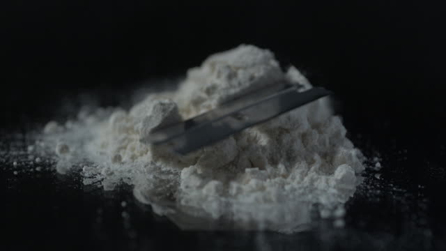 Razor blade falls on pile of cocaine