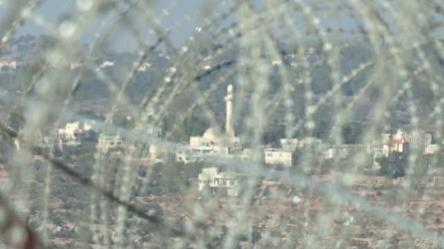 vídeos de stock, filmes e b-roll de razor wire and mosque, israel and palestine - boundary