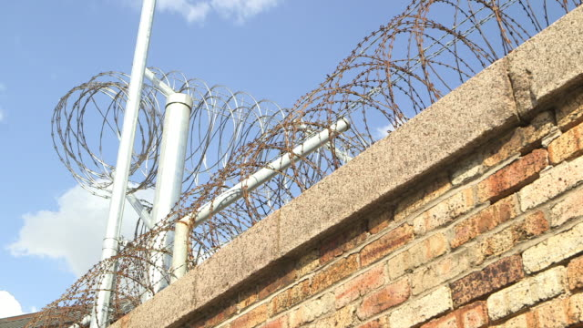 razor wire in front of penitentiary wall - barbed wire stock videos & royalty-free footage