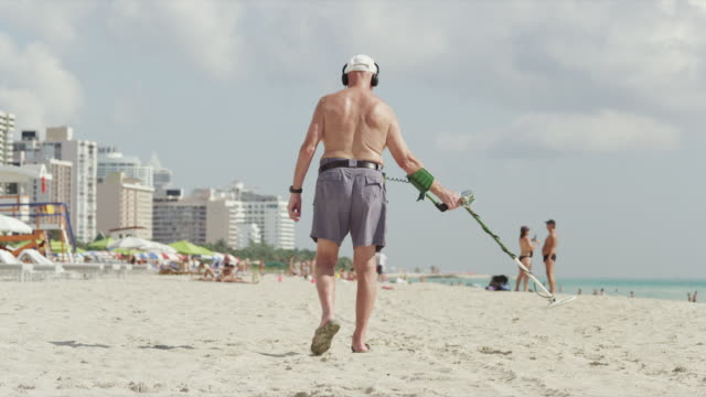 ws rea view of man with metal detector walking on beach / south beach, miami, florida, usa - 金属探知機点の映像素材/bロール
