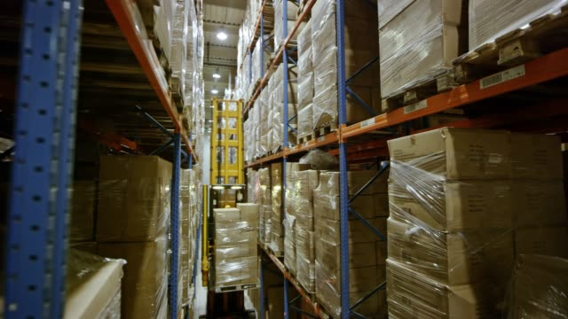 ds reach truck driving a pallet down the warehouse aisle - packaging stock videos & royalty-free footage