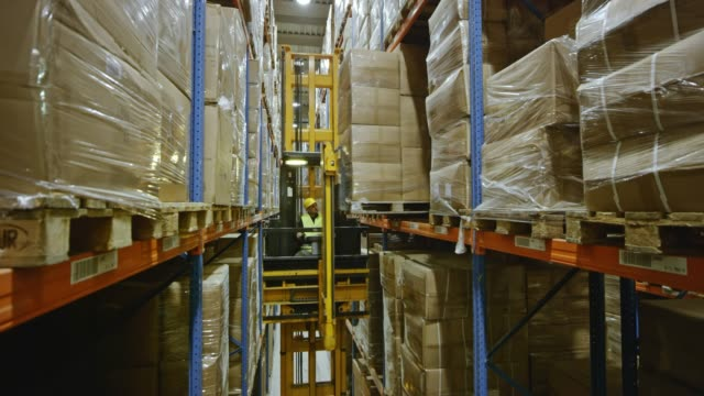 DS Reach truck placing a pallet onto the rack shelf in the warehouse aisle