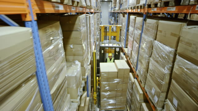 DS Reach truck raising the forklift operator and the pallet up the highest shelf