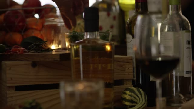 Reaching for a green bean on side table at a party with wine, brandy and snacks
