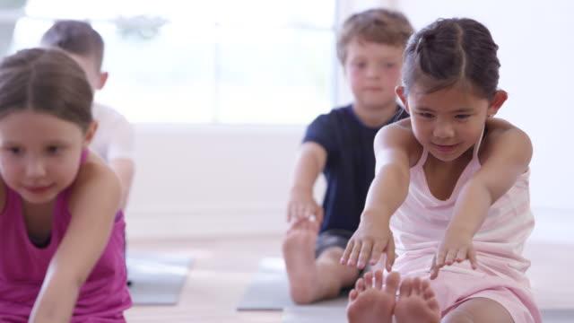 vídeos de stock, filmes e b-roll de alcançando seus dedos em crianças fitness - dedo do pé humano
